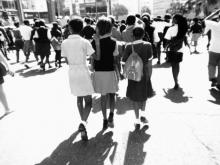 Three South African students walk to class hand-in-hand