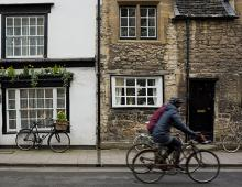 Two bikers bike past a historic building